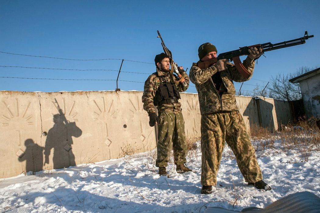 UKRAINE. Donetsk, East Ukraine. December 3, 2014. A Muslim fighter from Dagastan (rear) who came to help the Ukranian Christian separatists, seen at a separatist shooting range in the Petrovskyi neighbourhood.