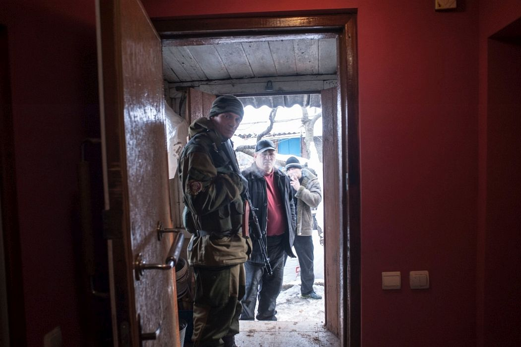 UKRAINE. Staromykhailivka, East Ukraine. December 3, 2014. Separatist inside house of a coal miner damaged by shelling from the Ukrainian army, which continues to fire mortars and incendiary rockets at areas controlled by Russian-backed separatists often hitting civilian neighborhoods.