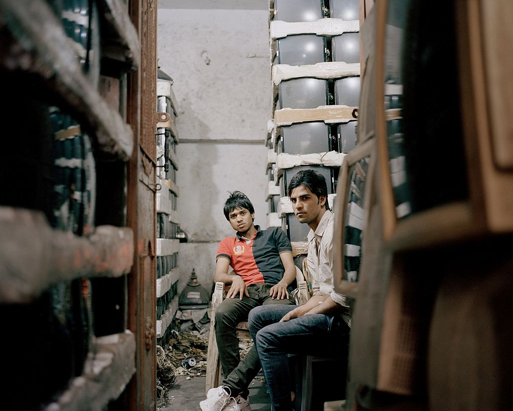 Old Seelampur, New Delhi, India. Two young men during a break in a warehouse full of old cathode ray tube monitors. These types of devices contain polluting and toxic substances like lead, cadmium, hexavalent chromium and Brominated Flame Retardants (BFRs). A prolonged exposure to these compounds can cause serious problems for the environment and for human health.