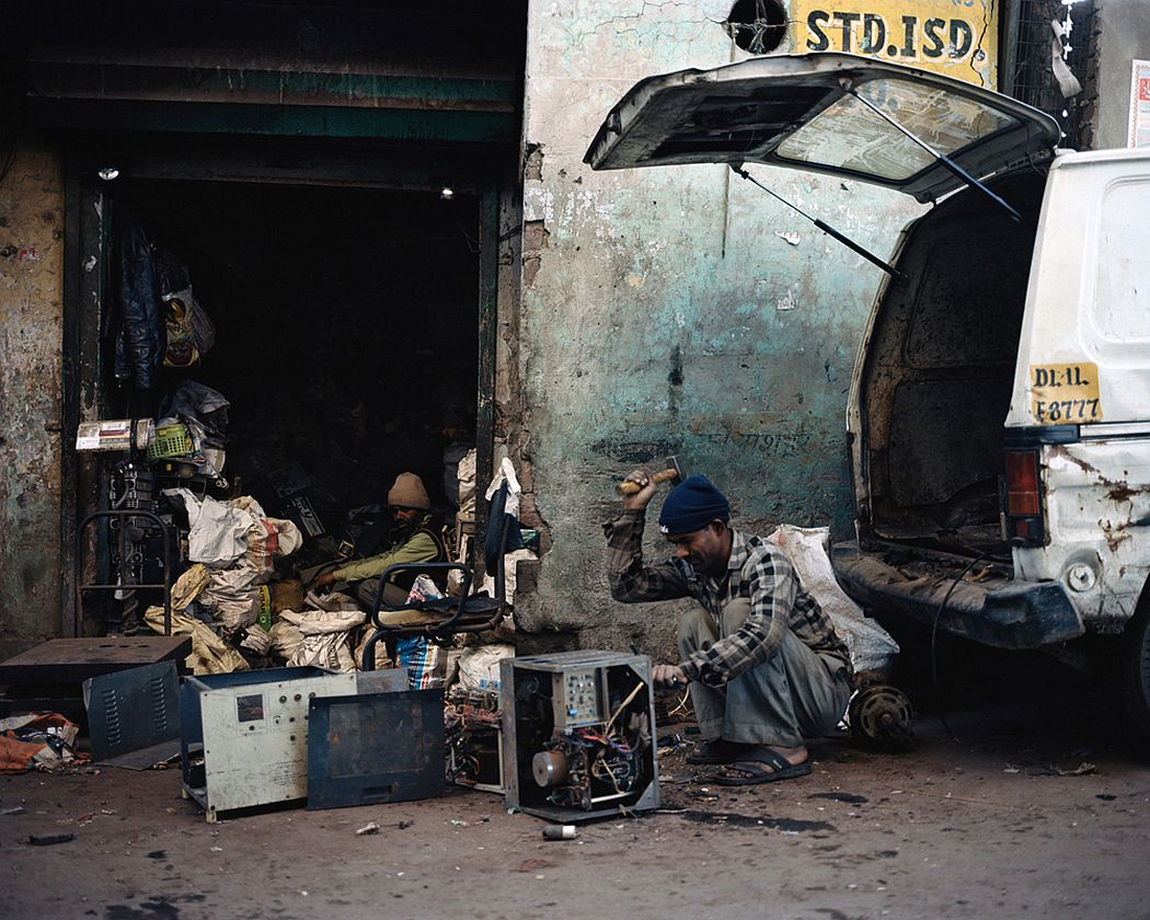 Old Seelampur, New Delhi, India. Workers in front of a warehouse used to dismantle electronic devices. They separate the components and extract the valuable parts to sell.