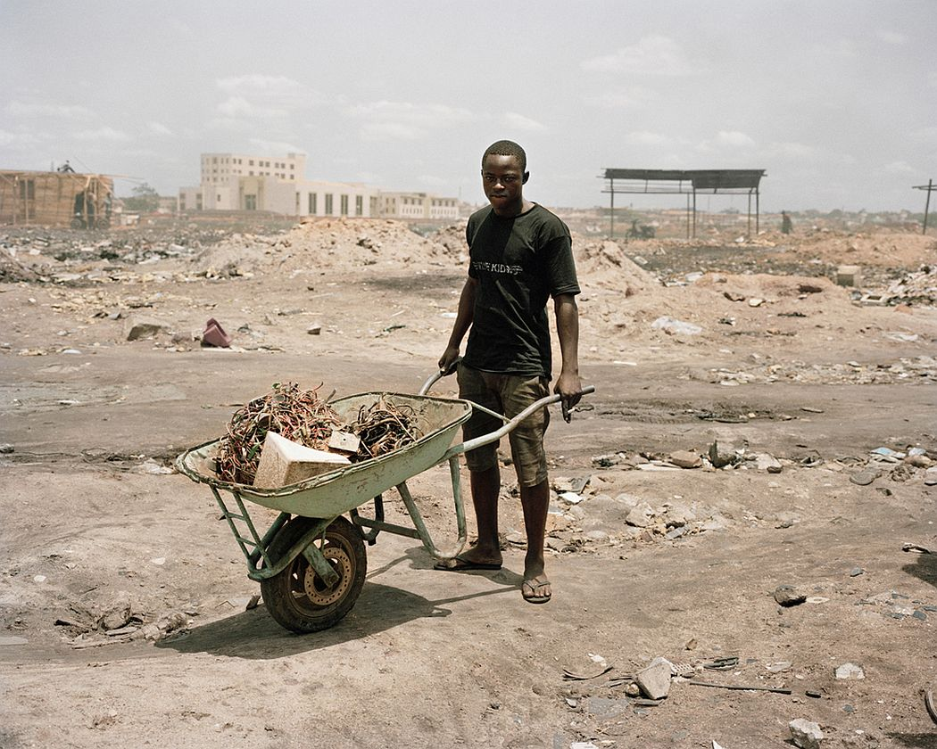 Agbobloshie, Accra, Ghana. A young man is transporting electric materials ready to be burnt. The materials treated in the Agbobloshie landfill contain substances that are highly toxic for the environment and for human health. Cadmium, lead, phthalates, antimony, PCBs (polychlorinated biphenyls), chlorobenzenes, Polybrominated diphenyl ethers (PBDEs), triphenyl phosphate (TPP), Brominated Flame Retardants (BFRs).