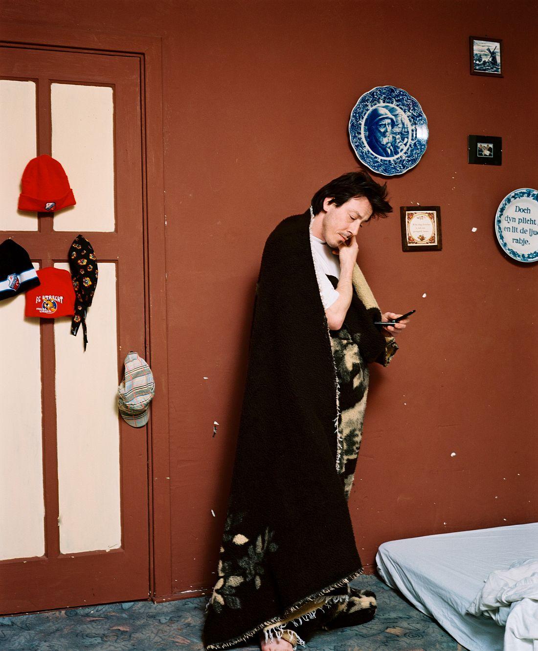 Utrecht, NEDERLAND, 2008 - Kid belt zijn moeder vanuit zijn slaapkamer in de Utrechtse volkswijk Ondiep. Omdat hij zelf nooit beltegoed heeft, is hij afhankelijk van de telefoons van zijn buren. Niet zelden staat hij direct nadat hij is opgestaan en vrijwel alleen gewikkeld in een deken bij hen voor de deur om te vragen of hij even mag bellen..© ROB HORNSTRA / +31 6 14365936..Utrecht, NETHERLANDS, 2008 - .© ROB HORNSTRA / +31 6 14365936
