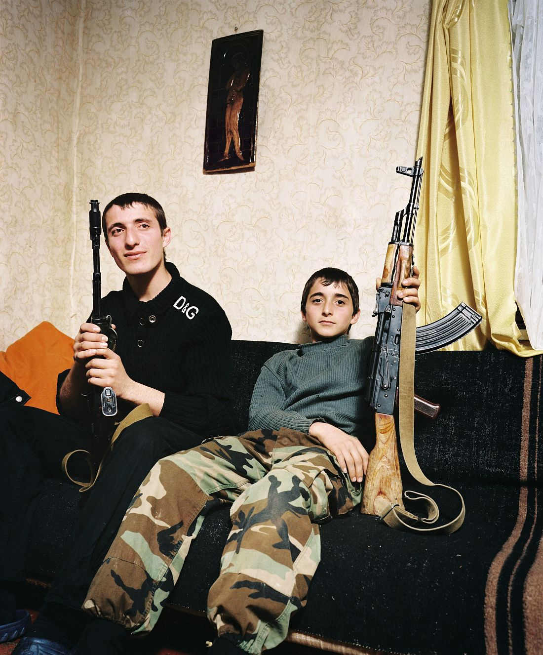Kuabchara, ABKHAZIA, 2009 - Brothers Zashrikwa (17) and Edrese (14) pose proudly with a Kalashnikov on the sofa in their aunt and uncle's house. They live in the Kodori Valley, a remote mountainous region on the border between Abkhazia and Georgia. In August 2008, Abkhazia gained control of the officially demilitarised Kodori Valley. The valley's 2,000 Georgian inhabitants fled over the border. A few families refused to be driven out: 'We are mountain people. Borders don't mean very much to us. But if I had to choose between a Georgian and an Abkhazian passport, I would choose a Georgian one.' © ROB HORNSTRA/+31 6 14365936