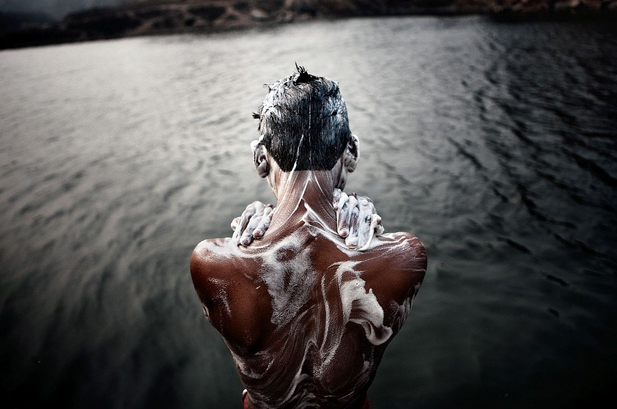 A miner bathing in the river to clean his skin from coal dust and pollution.