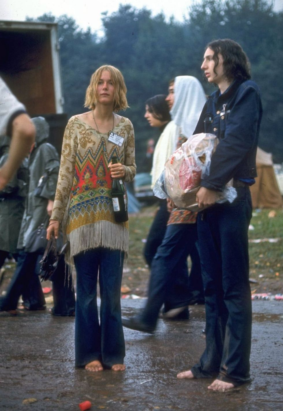 Hippie couple standing barefoot on a road holding a bundle & wine bottle