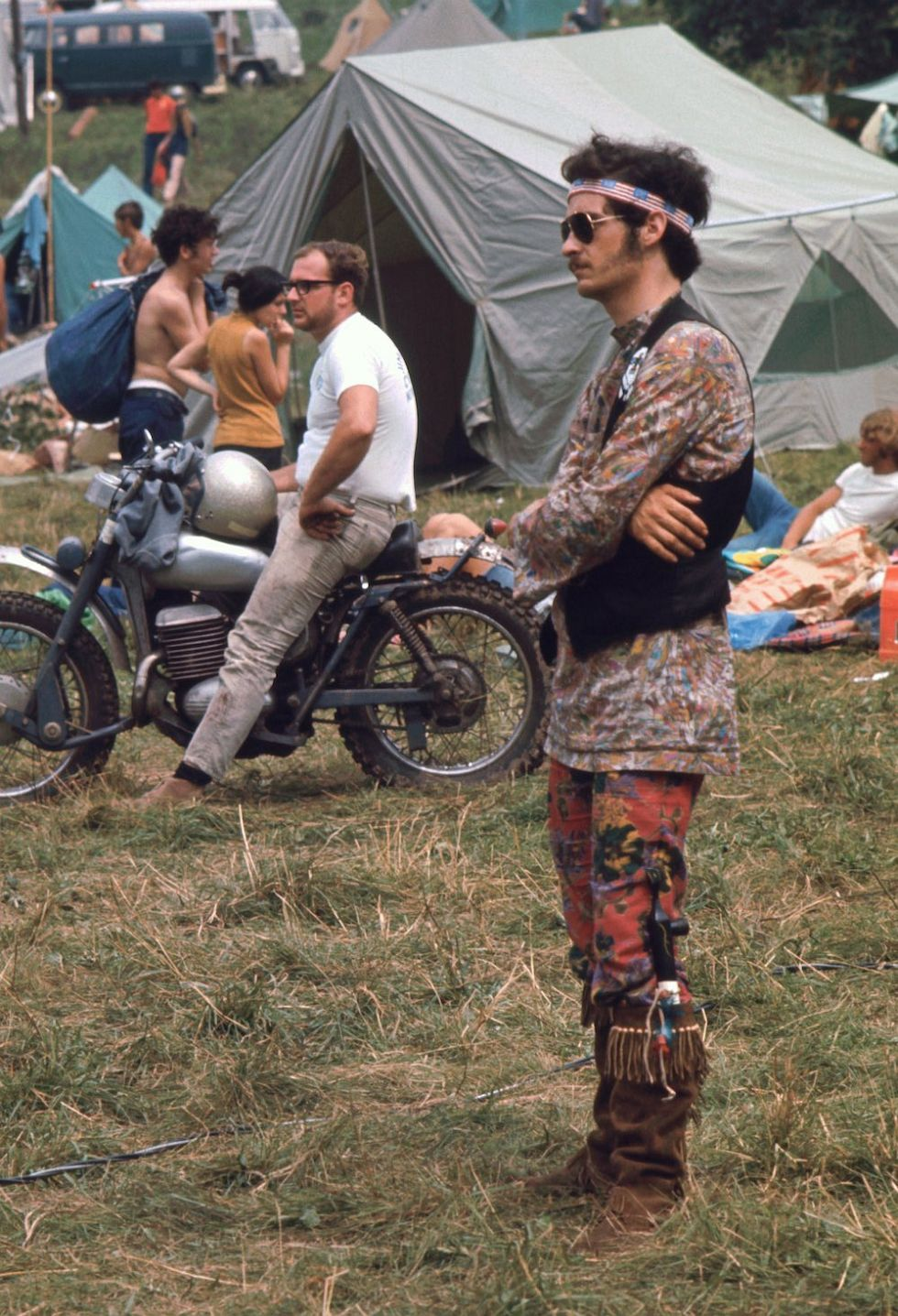 View of an unidentified festival goer as he stands, arms crossed, and watches a performace during the Woodstock Music and Arts Fair, Bethel, New York, August 1969. He is dressed in mis-matched flower print shirt and leggings, a headband made of American flags, a suede vest, and fringed, suede boots, in one of which is a long pipe. Sunglasses, mutton chops, and a mustache complete his outfit. The festival ran from August 15 to 18. (Photo by Ralph Ackerman/Getty Images)