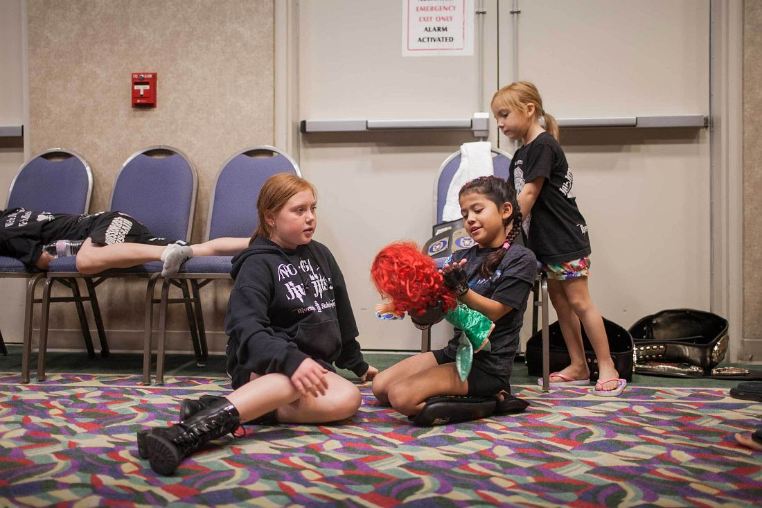 "Regina ""Black Widow"" Awana, 7, playing with her favorite doll, Ariel, with friends before her fights. She won all fights this night. United States Fight League(USFL) All-star Pankration show at Blue Water Casino in Parker, Arizona on 25th of October 2013. Photo: Miikka Pirinen"