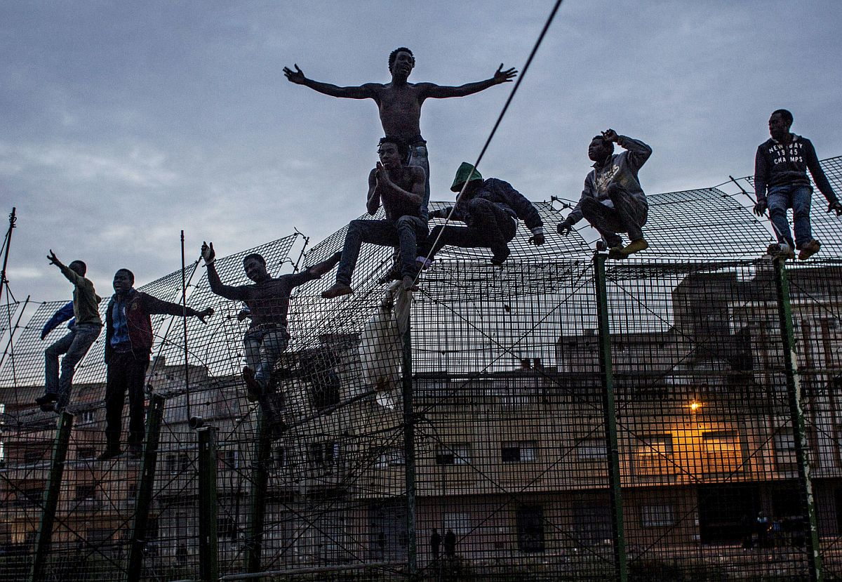 Young men from the Ivory Coast, on top of the fence that separates them from Europe, ask for clemency from the police who arrested them. Even though these immigrants were already in Spanish territory, they were deported illegally to Morocco.
