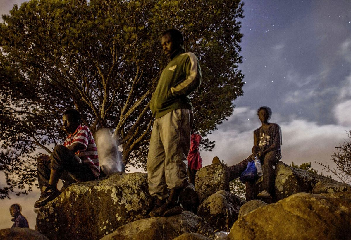A group of immigrants hide from Europe in the Gurugu Mountains, watching the lights of the Spanish city of Melilla.