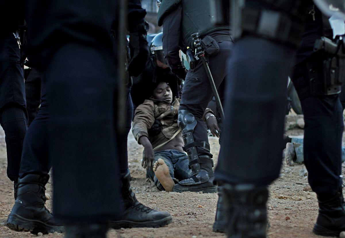 An injured immigrant, after struggling with the Spanish police to avoid deportation.