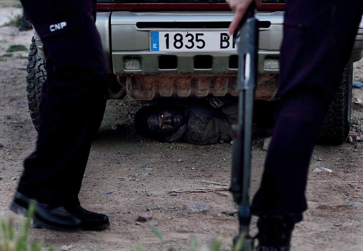 To avoid deportation, an immigrant hides under a car after jumping the fence that separated him from Europe.