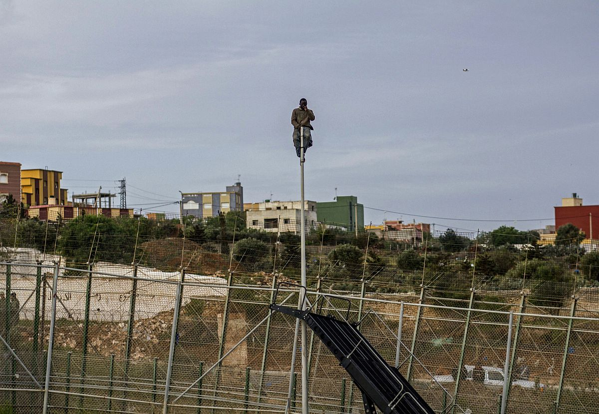 After jumping the fence, an immigrant climbed a lamppost on the Spanish side to avoid being caught and deported by the Spanish police. After spending several hours up the lamppost, he asks for some water.