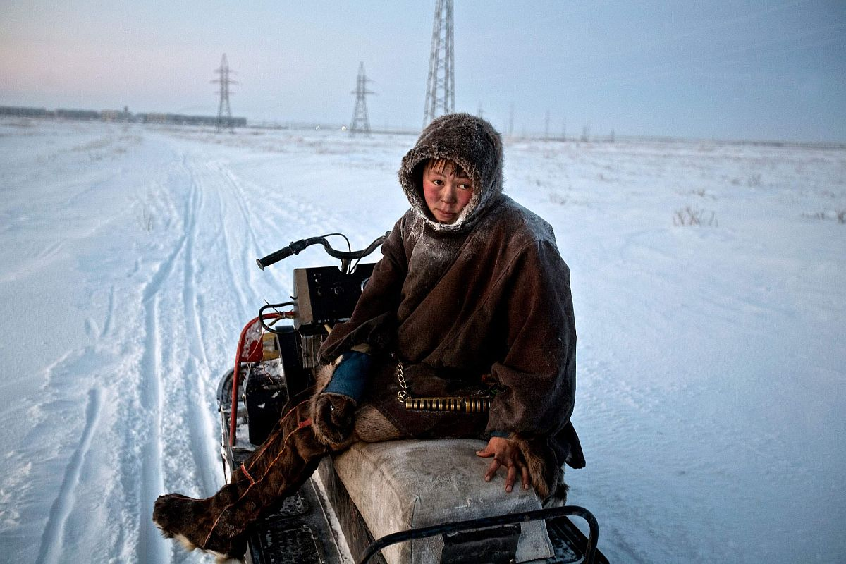 Reindeer herder Simyon, travels by sled from his chum (tent) towards Vorkuta to buy supplies. Construction of gas pipelines and industrial complexes are threatening the herders' way of life, forcing them to travel further afield in search of pastures. Vorkuta is a coal mining and former Gulag town 1,200 miles northeast of Moscow, beyond the Arctic Circle, where temperatures in winter drop to -50C. Here, whole villages are being slowly deserted and reclaimed by snow, while the financial crisis is squeezing coalmining companies that already struggle to find workers, January 2009.