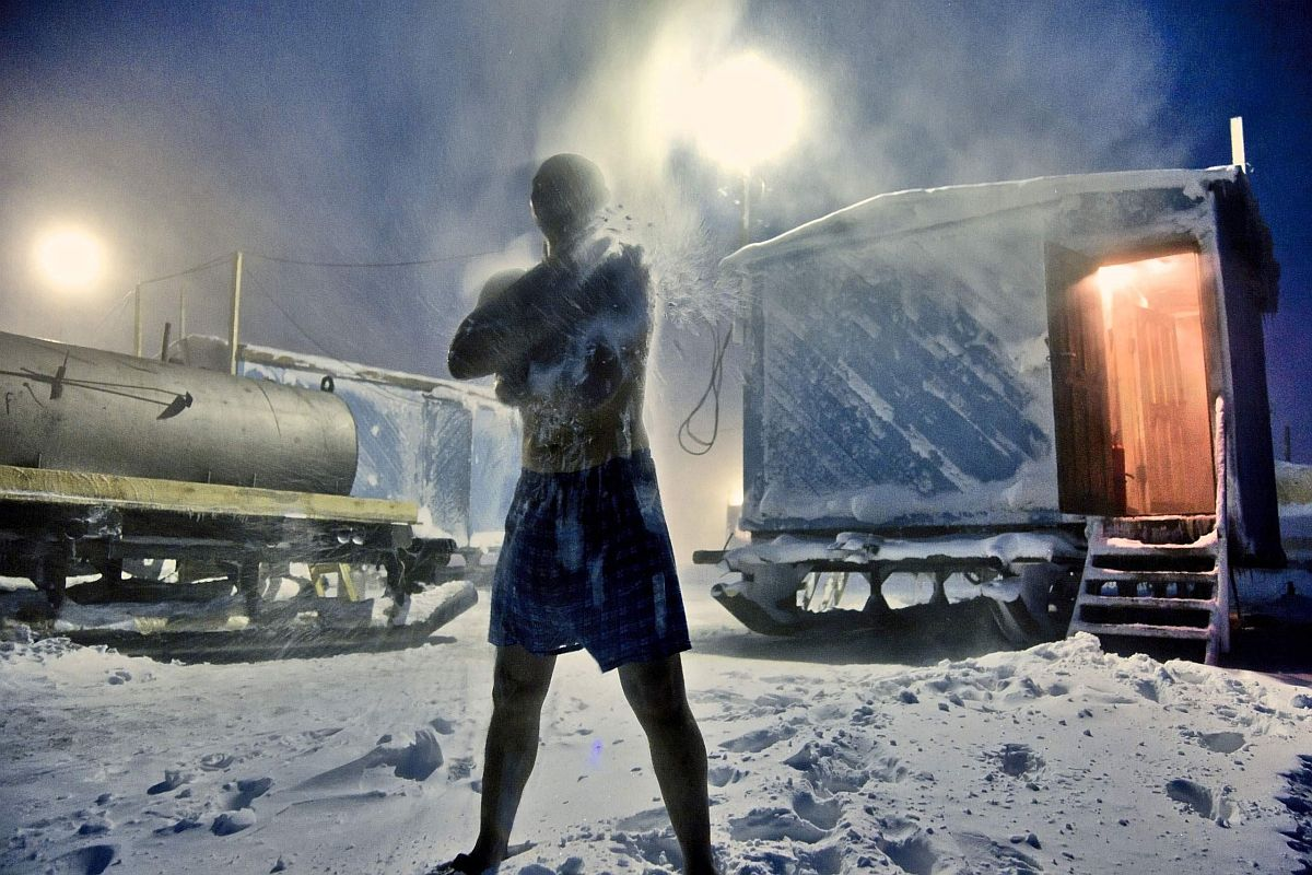 A man working on the frontier of Arctic gas and oil exploration rubs himself with snow during sauna in the Arctic tundra. The water is heated by the diesel tank on the left of the picture. Typically, these men work in the cold, isolated wilderness for the entire winter, returning to civilisation only in spring.