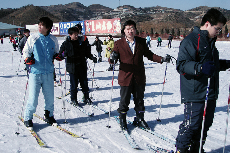 A Chinese man wearing a suit enjoys a day out skiing at Linhai Ski resort in Dalian.