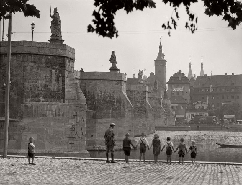 Bridge with statues seen from below, group of children holding hands, Würzburg, 1925